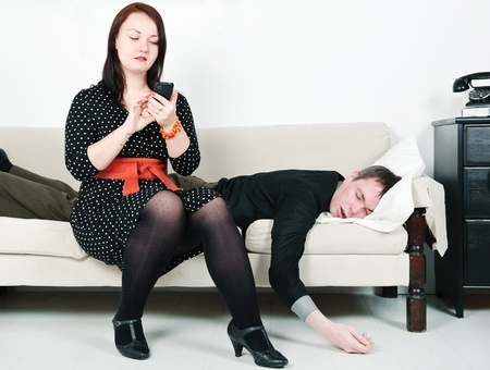 Woman checking telephone of her sleeping man
