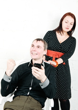 Jealous woman looking at her man chatting on telephone Stock Photo - 17276843