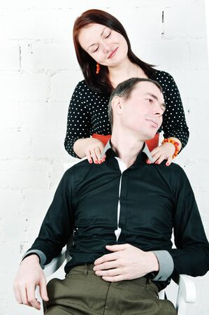 Relaxing man receiving shoulder massage from his woman at home photo