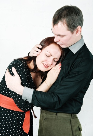 Man hugging and comforting his crying woman photo