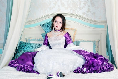 Beautiful young woman in medieval dress sitting on the bed Stock Photo - 17416932