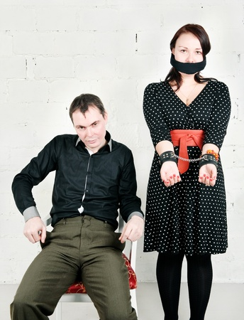 Imperious man and woman with tied mouth in handcuffs