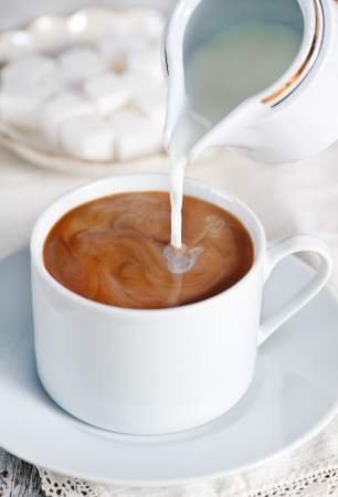 Milk pouring into cup of coffee and sugar Stock Photo