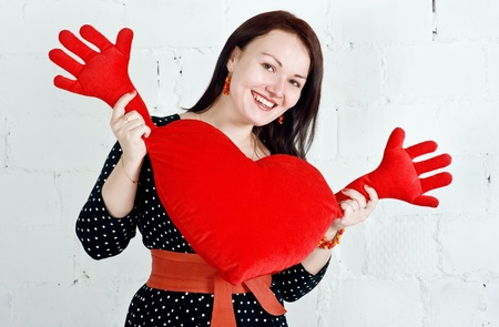 Beautiful woman with red heart toy photo