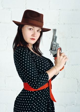 Portrait of serious woman in brown hat with gun photo