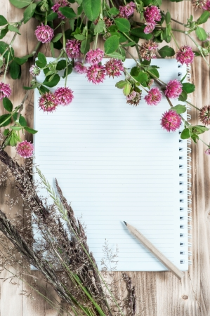 Open notebook, clover, herbs and pencil on the wooden background photo