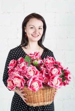 Beautiful woman with red flowers in the wattled basket photo