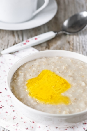 A bowl of hot oatmeal with butter on the old wooden background Stock Photo - 20013411