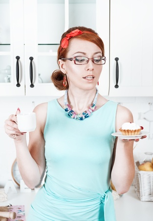 Beautiful woman with cake and coffee on the kitchen photo