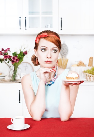 Sad beautiful young woman looking on cake in the kitchen photo