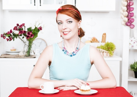 Beautiful smiling woman with red hair on the kitchen photo