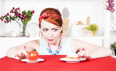 Beautiful woman choosing between healthy food and cake photo