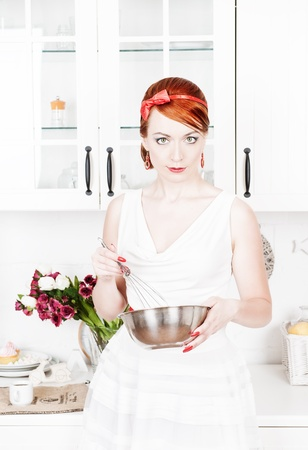 Beautiful housewife with utensils  on the kitchen photo
