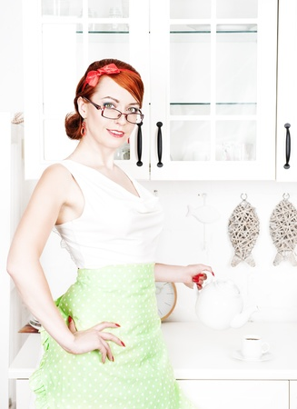 Portrait of stylish beautiful housewife pouring tea photo