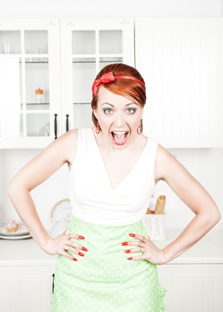 Angry screaming housewife on the kitchen photo