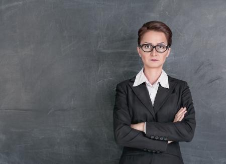 educadores: Estricto profesor en el fondo de pizarra de la escuela