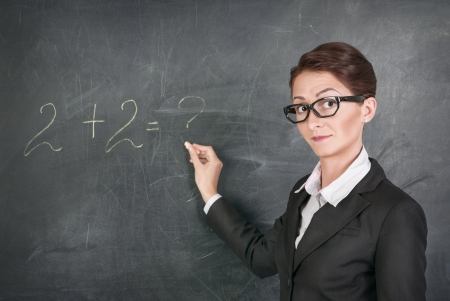 Woman teacher in glasses teaching maths photo
