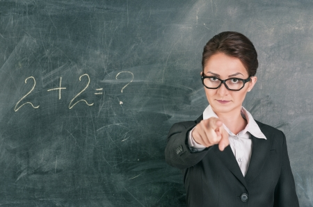 Woman teacher in glasses teaching maths and pointing on someone photo