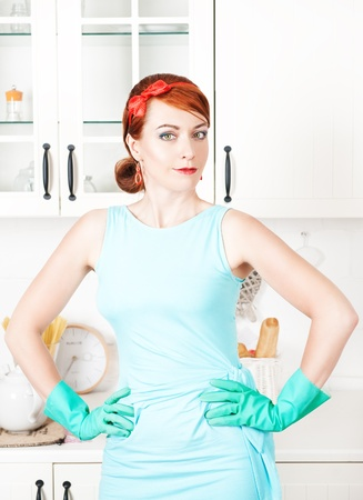 Smiling housewife with rubber gloves on the kitchen photo