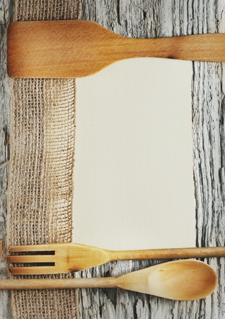 Utensils, sheet of paper and ribbon on the old wooden background photo