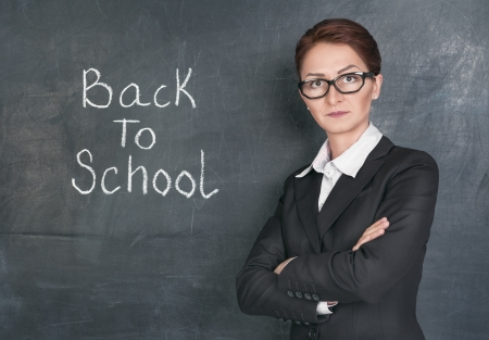 Strict teacher on the school blackboard background with phrase Back to school photo