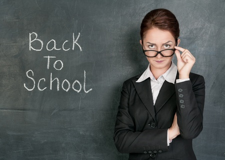 Strict teacher on the school blackboard background with phrase Back to school