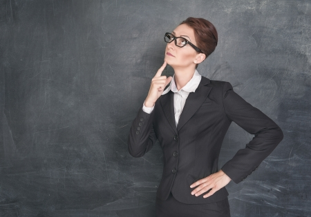 stringent: Thoughtful teacher on the school blackboard background Stock Photo