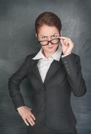 Strict teacher looking at someone on the school blackboard background Foto de archivo