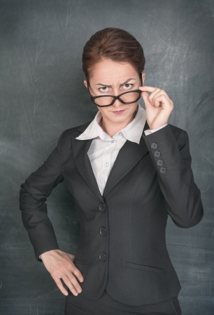 rigorous: Strict teacher looking at someone on the school blackboard background Stock Photo