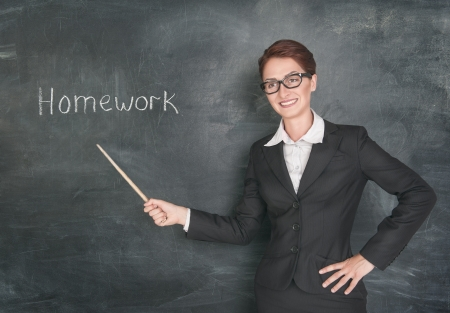 Smiling teacher with pointer and phrase Homework on blackboard chalkboard photo