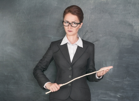 Strict teacher with wooden stick looking at someone