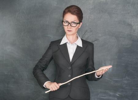 Strikte leraar met houten stok op zoek naar iemand