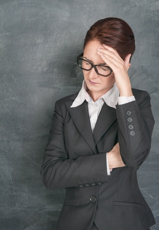 Teacher with headache on the school blackboard background photo