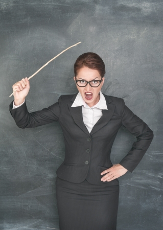 Angry screaming teacher with wooden stick photo