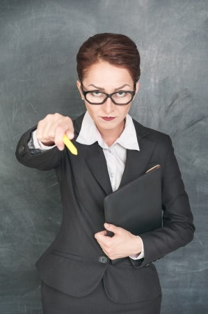 Strict teacher in glasses pointing on someone with chalk
