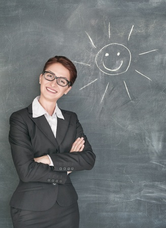 Happy teacher in glasses and smiling sun on the chalkboard