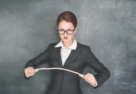 Angry teacher in glasses with wooden stick photo