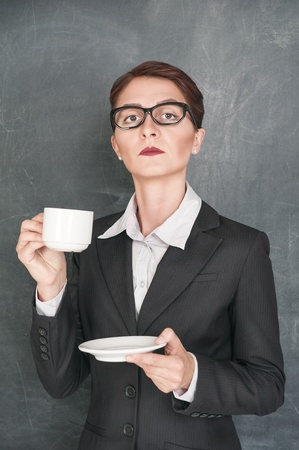 Serious teacher in glasses with cup of coffee photo