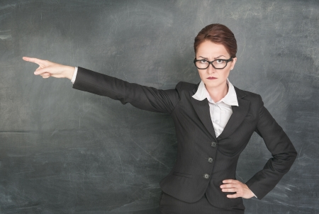 bad woman: Angry teacher in glasses pointing out