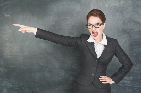 Angry screaming teacher in glasses pointing out photo