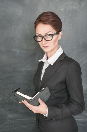 stringent: Serious teacher in glasses with organizer