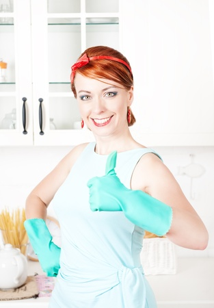 Happy housewife with rubber gloves showing thumbs up on the kitchen photo