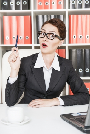 Business woman in glasses having an idea photo