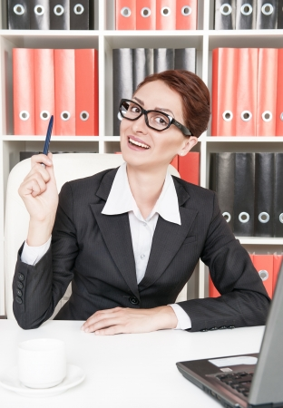 Happy business woman in glasses having an idea photo