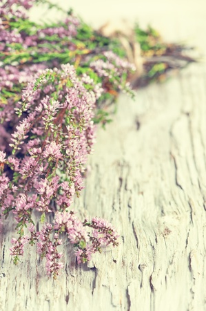 Bouquet of heather on the old wooden background photo