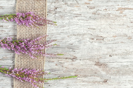 Old rough wooden background with heather and sacking ribbon