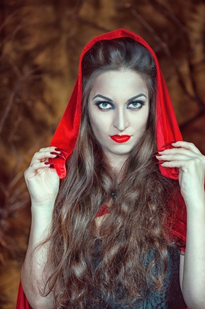 Beautiful halloween woman with long hair in red cloak