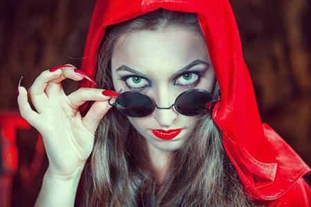 Mooie halloween vrouw in zwarte glazen en rode mantel Stockfoto