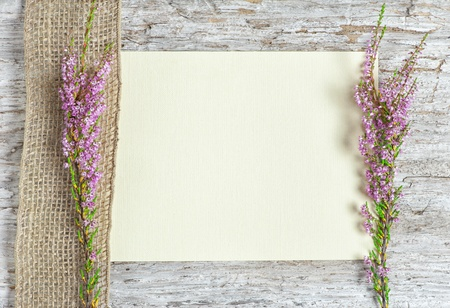 Old rough wooden background with canvas, heather and sacking ribbon photo