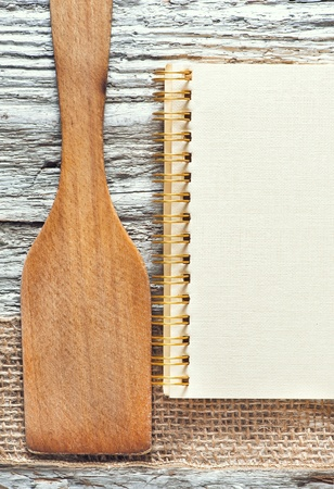 Wooden spatula, notebook and ribbon on the old wooden background photo